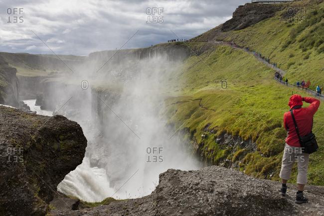 Tourist standing at edge of Gullfoss waterfall, Iceland