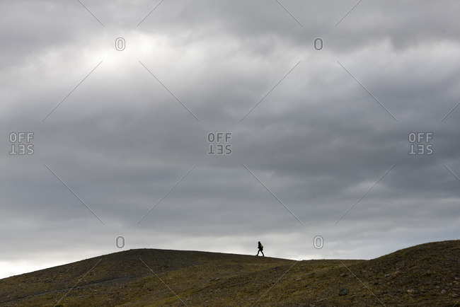 Iceland, person walking along barren hilltop