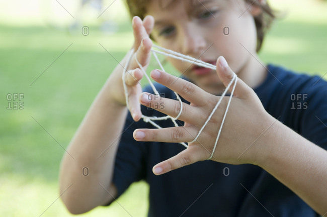 Boy playing cat's cradle, focus on hands