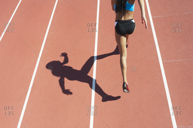Female athlete running on track, rear view