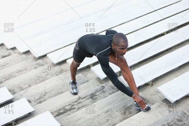 Man stretching on bleacher steps