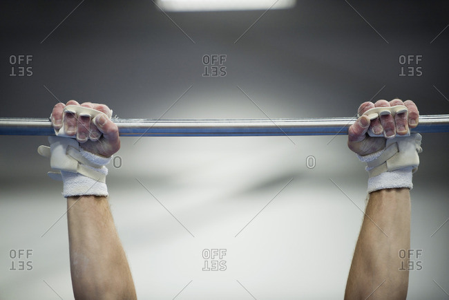 Gymnast's arms gripping horizontal bar, cropped