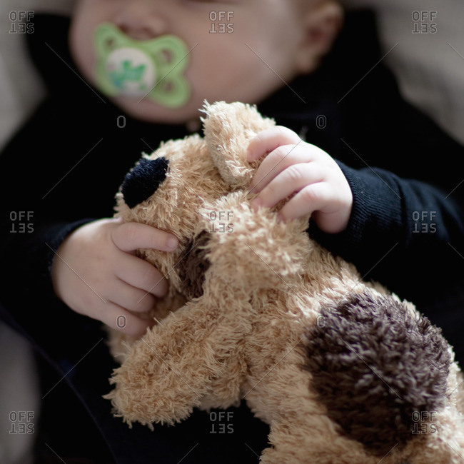 Baby boy holding stuffed toy, cropped