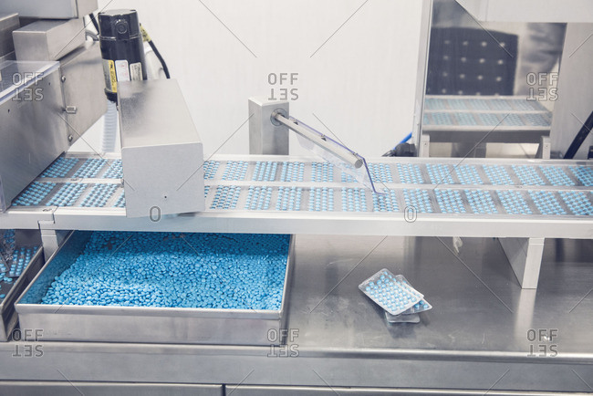 Tablet trays on conveyor belt entering blisterpack sealing machine