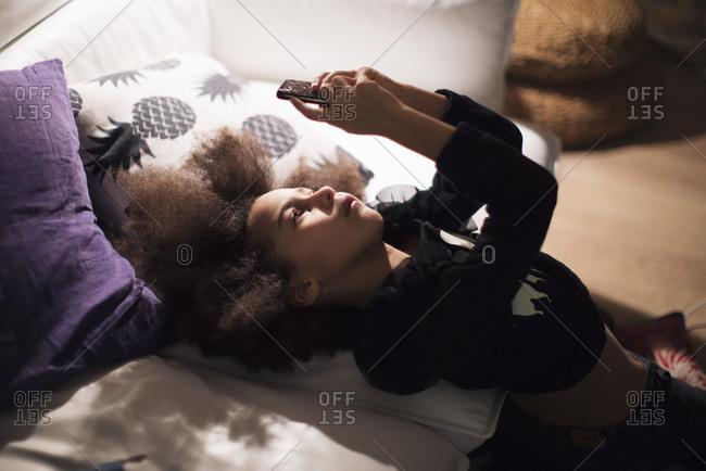 Girl reclining against sofa, engrossed in smartphone