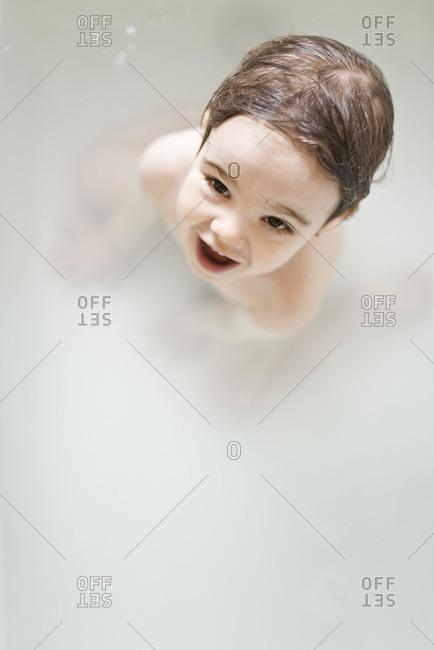 Toddler boy taking a bath, portrait