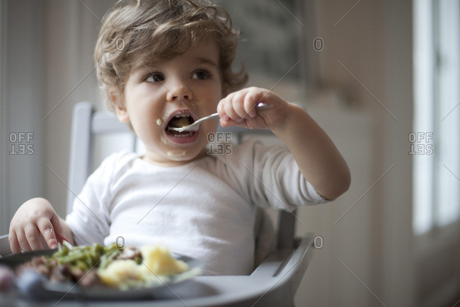 Toddler boy feeding himself - Offset