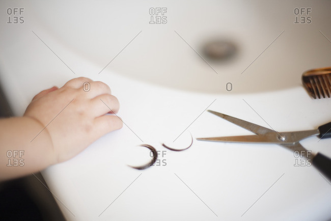 Child's hand resting on sink near scissors and locks of hair