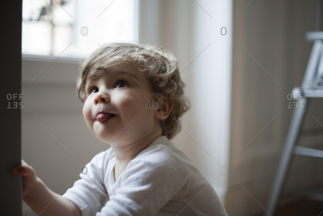 Toddler boy sticking out tongue, looking up, portrait