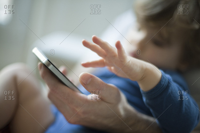 Toddler touching father's cell phone
