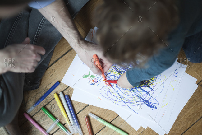 Father and toddler drawing together on paper, high angle view