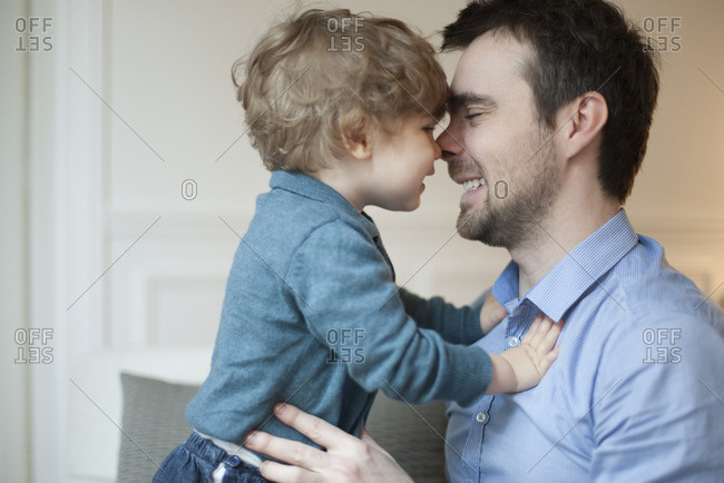 Father and toddler son nuzzling