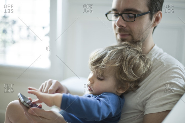 Toddler boy touching father's cell phone curiously