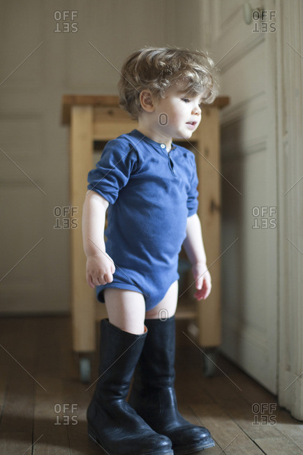 Toddler boy wearing father's boots