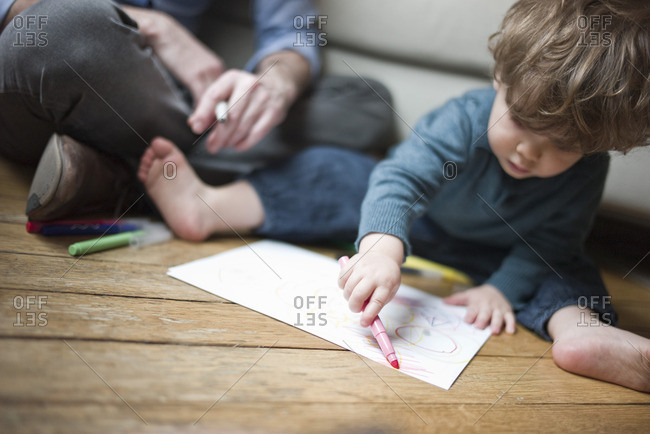 Toddler boy sitting on floor with parent, drawing on paper