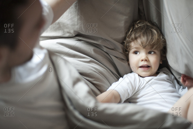 Toddler boy and father in bed