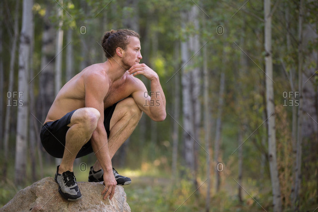 Man crouching on rock in woods