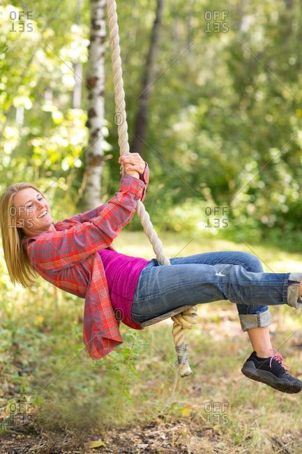 Woman swinging on rope swing