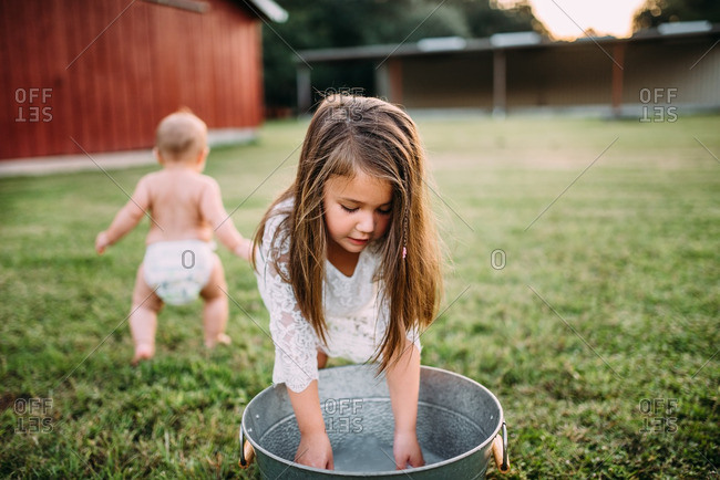 Girl playing in pan of water outdoors on lawn