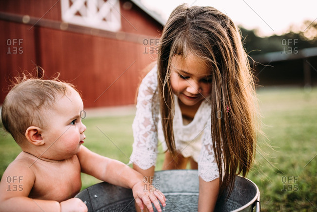 Baby looks at sister as they play in pan of water on lawn