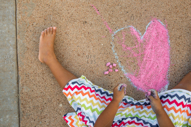 Overhead view of girl drawing on a sidewalk with colorful chalk