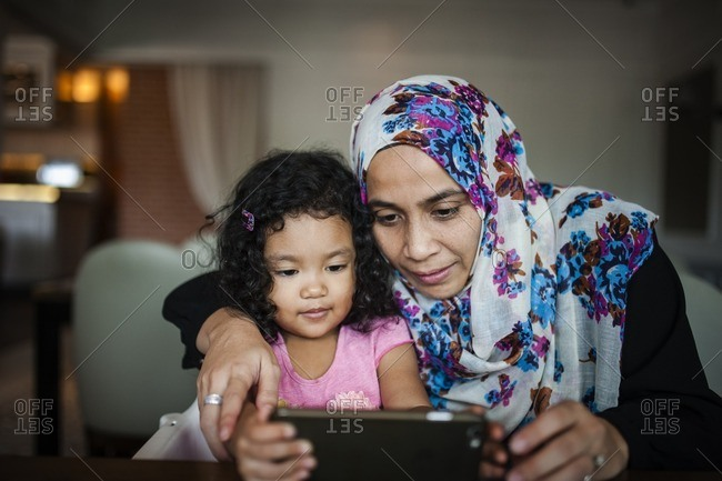 Woman using smartphone with toddler