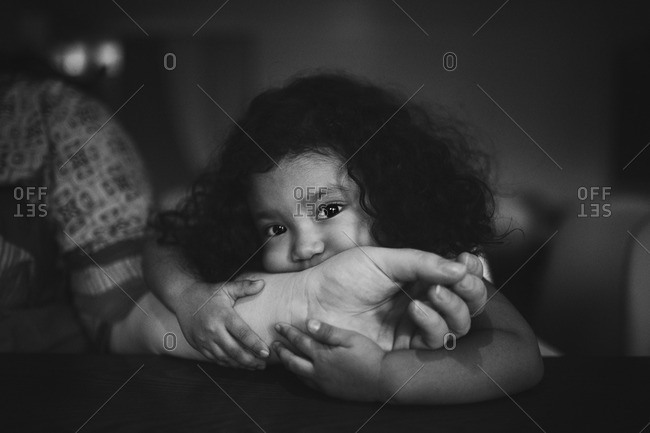 Toddler girl holding her mother's arm