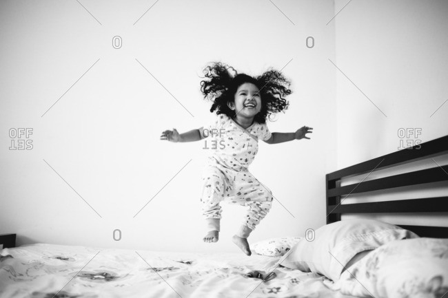 Joyous toddler girl jumping on bed