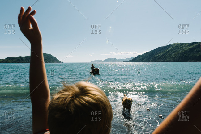 Boy greeting dog and boat in ocean