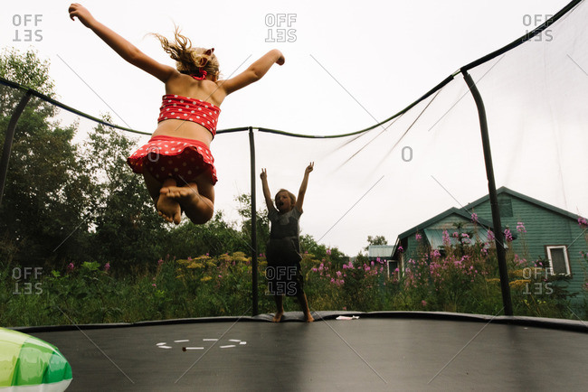 Two kids bouncing on trampoline