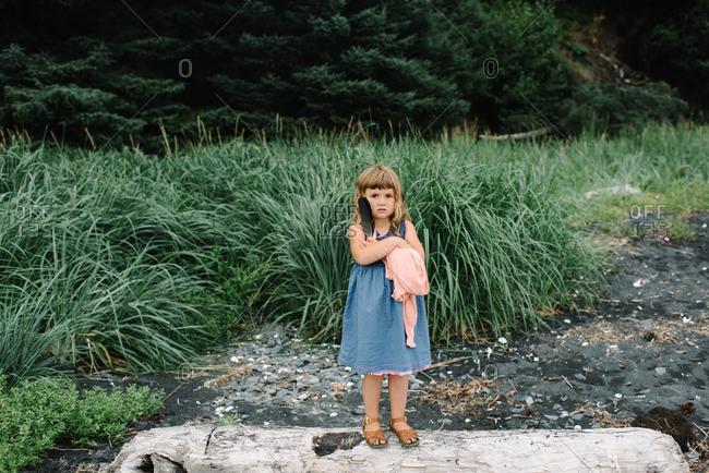 Girl on log holding items