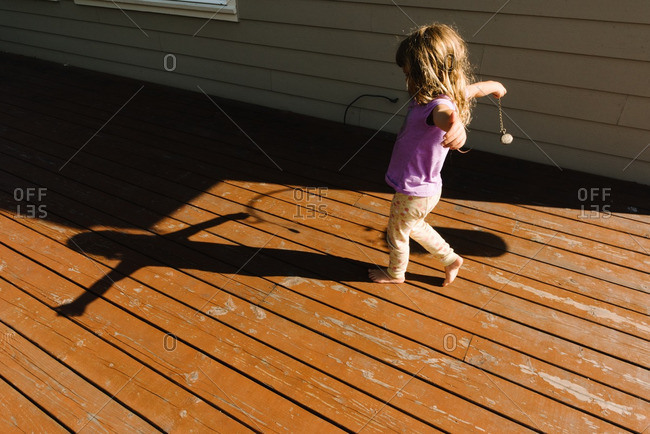 Girl making shadow shapes on deck