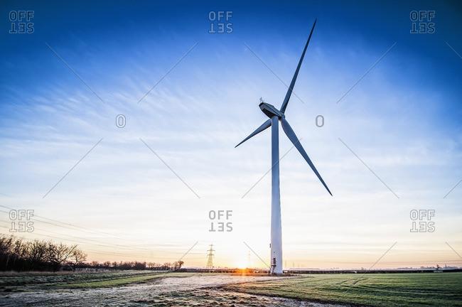 Wind turbine in snowy rural landscape