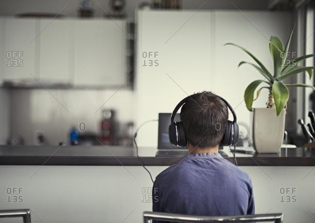 Mixed race boy listening to headphones in kitchen