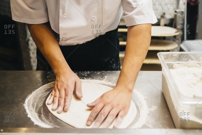 Chef shaping pizza dough in restaurant kitchen
