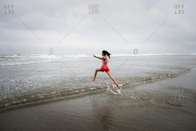 Mixed race girl running into ocean on beach