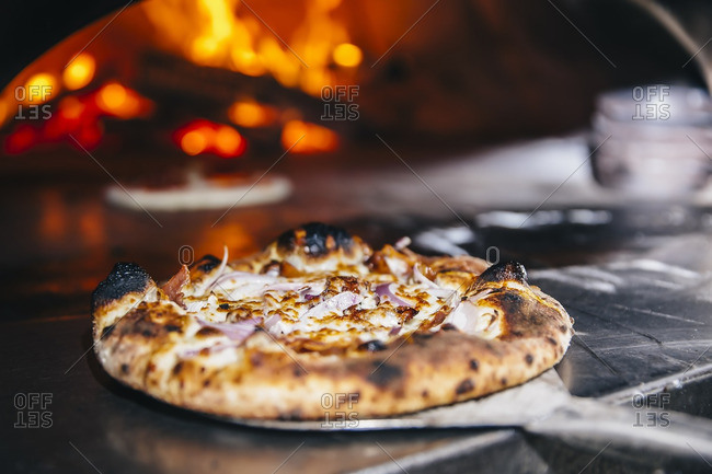 Pizza cooking in wood fired oven