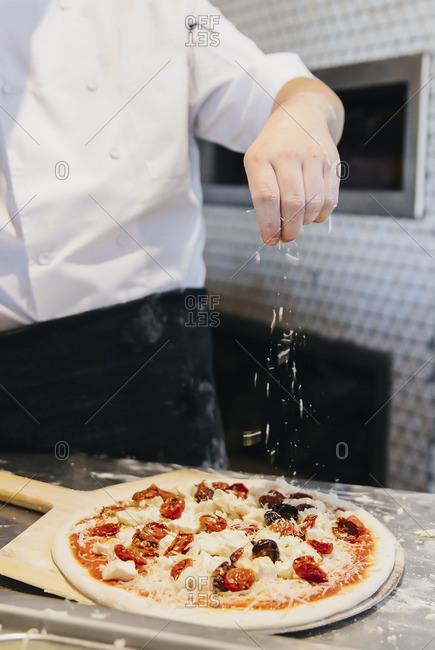 Chef making pizza in restaurant in kitchen