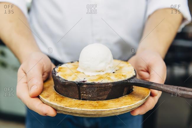 Caucasian waiter holding skillet dessert