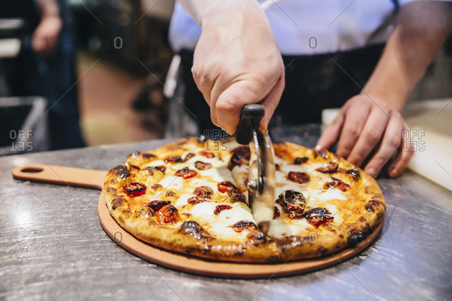 Chef slicing pizza in restaurant kitchen