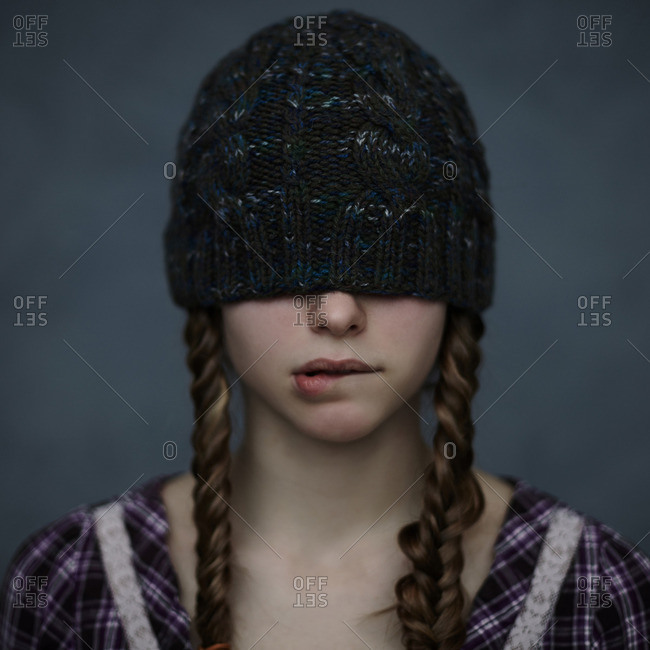 Caucasian girl wearing beanie hat over eyes