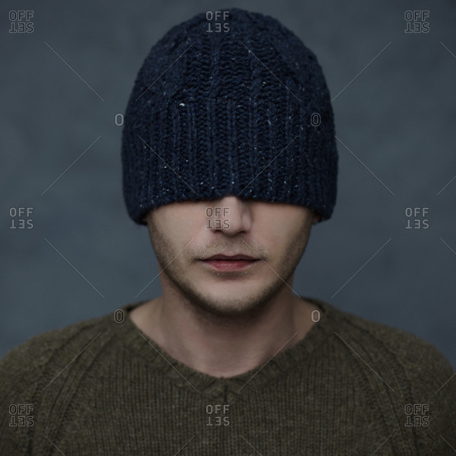 Caucasian man wearing beanie hat over eyes