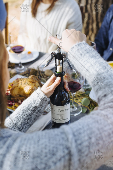 Woman opening bottle of wine outdoors