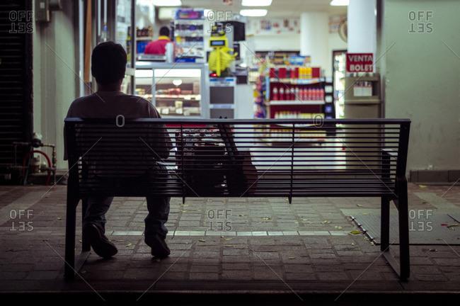 Man sitting on city bench at night