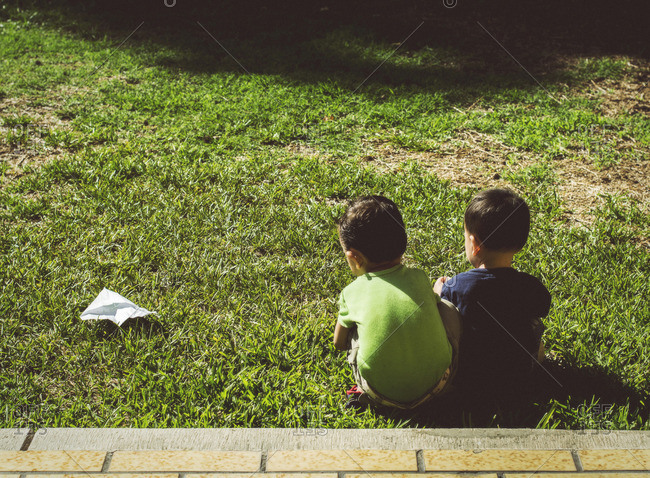 Hispanic brothers with paper airplane on lawn