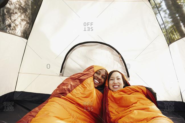 Multi-ethnic couple inside sleeping bags and tent