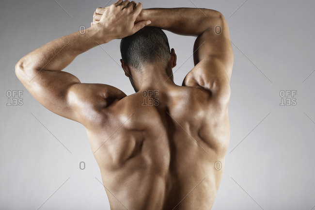 Bare chested mixed race man with arms raised