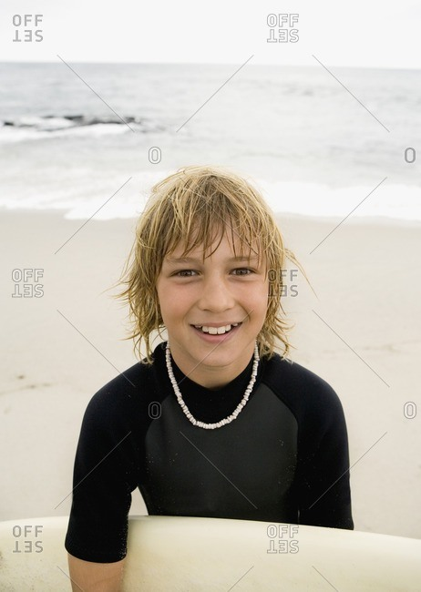 Boy holding surfboard at beach