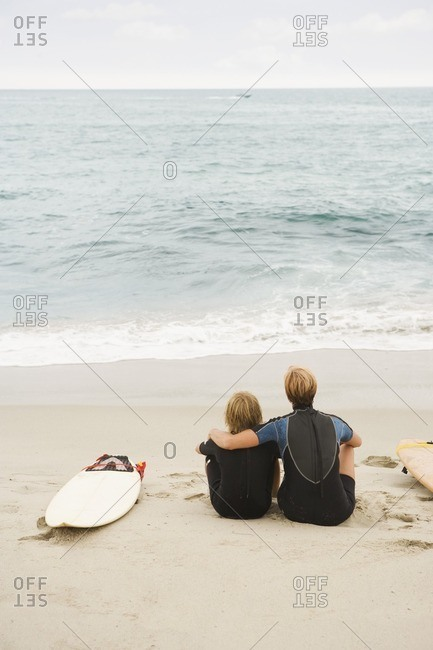 Mother and son sitting on beach next to surfboard