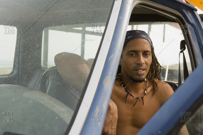 Bare chested Hispanic man sitting in cab of truck